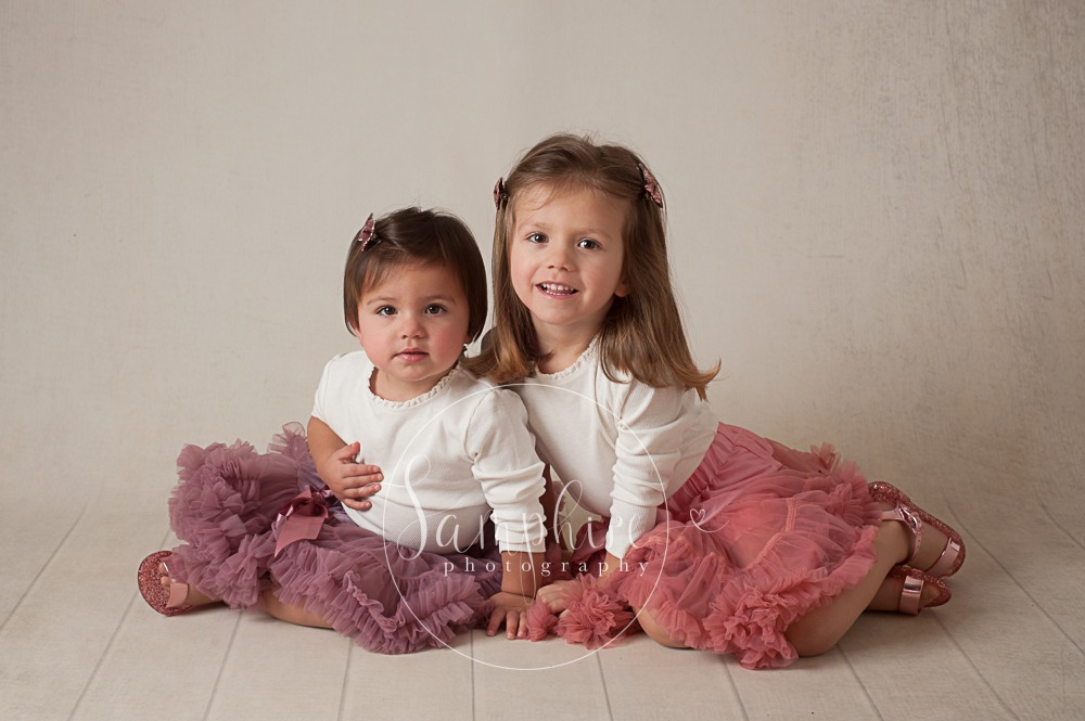 Samphire Photography studio portrait photo sisters siblings family smiles tutu purple pink Sussex