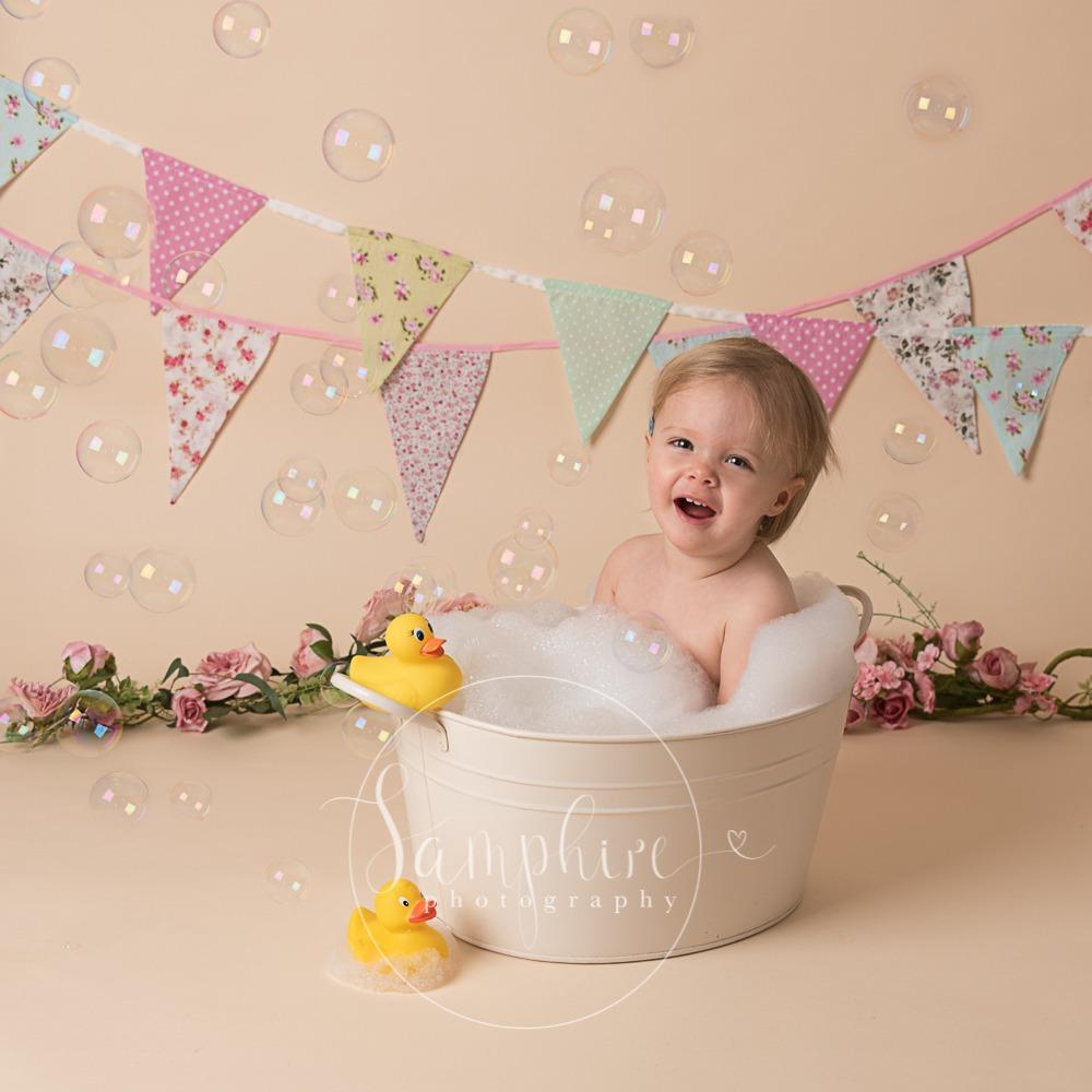 Cake Smash splash bubbles bath ducks bunting pink flowers photo sussex