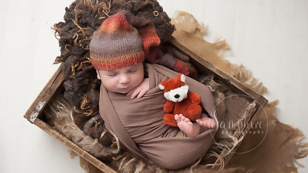 Samphire Sussex newborn photographer baby boy swaddled wrapped knitted hat brown