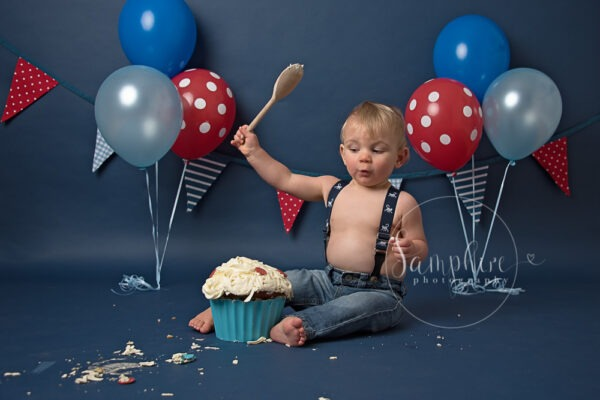 Bespoke cake smash photography, Sussex studio portrait happy boy first birthday blue red polka dot by Samphire Photography