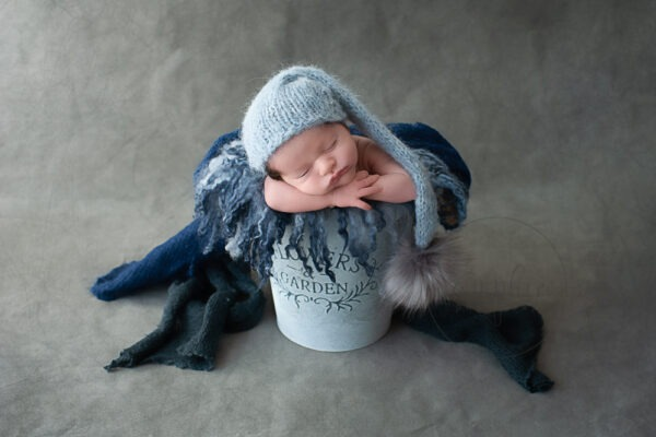 sleepy baby boy in blue knits and layers studio portrait newborn photographer sussex Samphire Photography