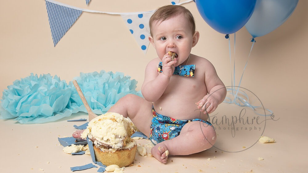 birthday boy in blue with balloons bunting cake smash photographer west sussex Samphire Photography