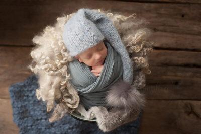 baby twins photographer Sussex newborn boy asleep knits wraps layers bobble hat studio portrait Samphire Photography