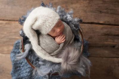 baby twins photographer Sussex newborn boy asleep blue grey knits wraps layers bobble hat studio portrait Samphire Photography