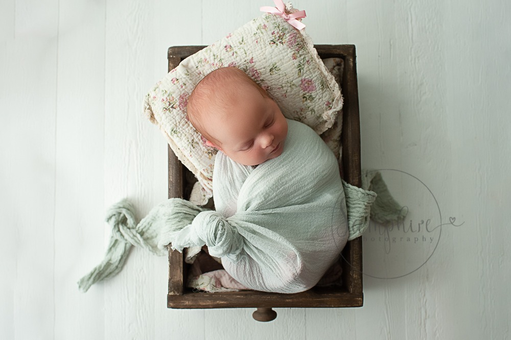 newborn baby photographs Sussex mint green warp pink floral pillow studio portraits by Samphire Photography