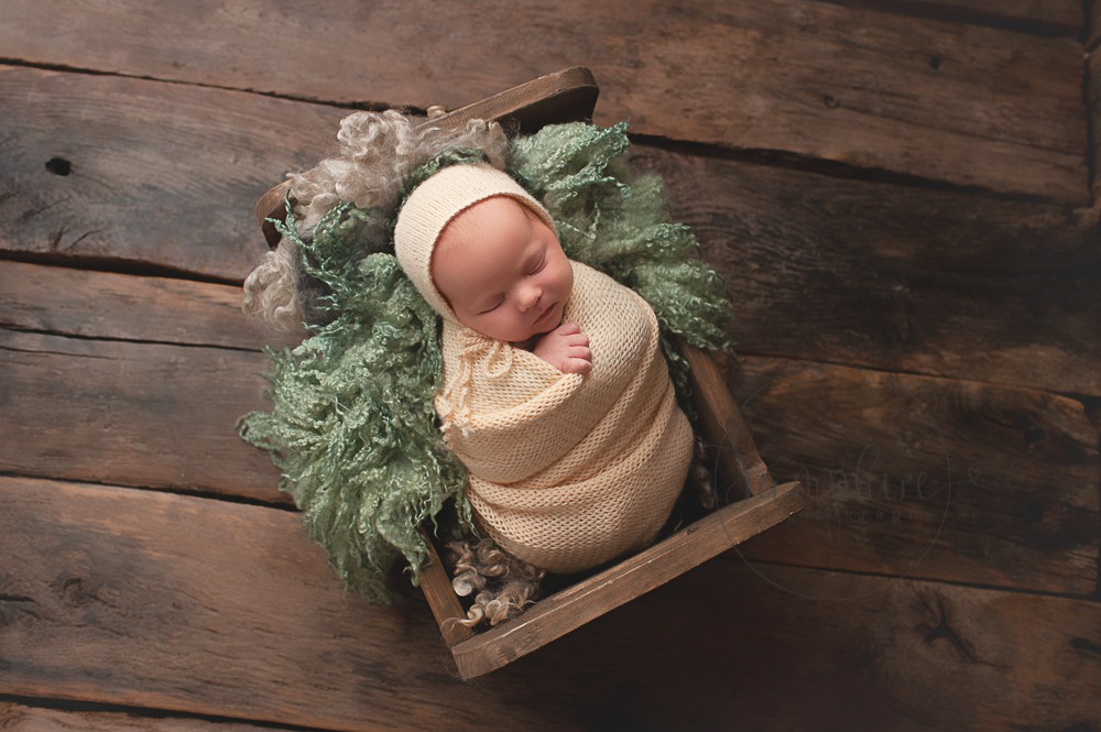 newborn baby photographs Sussex sleeping girl knitted bonnet pale yellow green curly layer wood background studio portraits by Samphire Photography