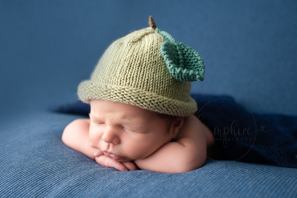 Experienced newborn photographer West Sussex sleeping baby boy knitted apple hat blue studio portrait Samphire Photography
