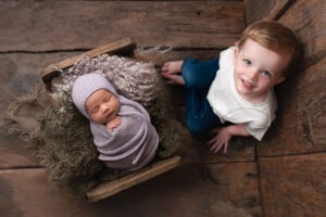 Professional Newborn Photographer Horsham asleep girl pink knit brother Samphire Photography