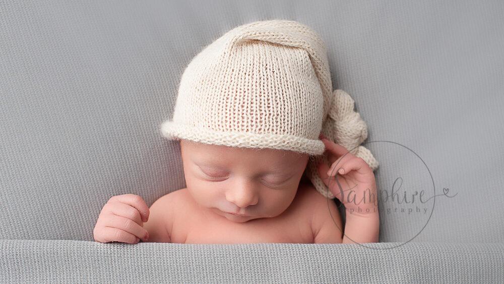 Professional Newborn Photographer Horsham baby boy asleep on grey wearing knitted hat Samphire Photography