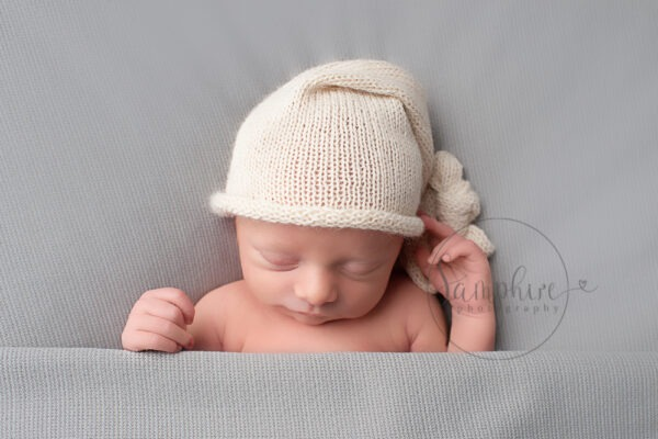 Professional Newborn Photographer Horsham baby boy asleep on grey wearing knitted hat Samphire Photography