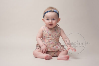 Baby's first year milestone portraits pink floral patterned romper headband Samphire Photography Sussex