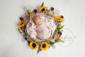 Baby's first year newborn portraits pink layers flowers basket Samphire Photography Sussex