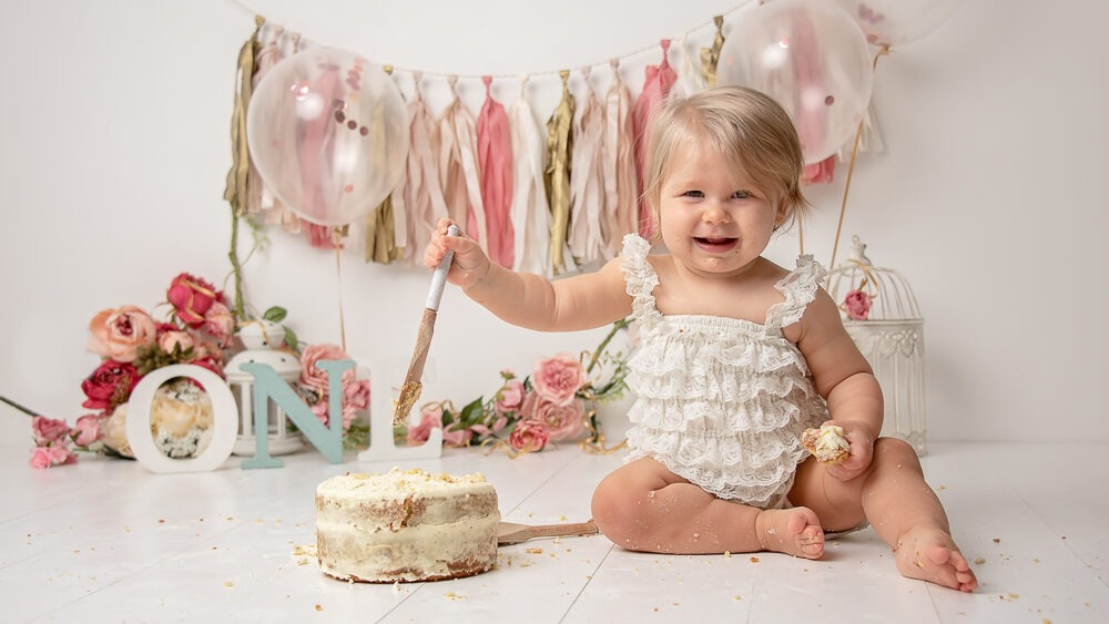 girly cake smash pink floral paper garland birthday Samphire Photography Horsham Sussex