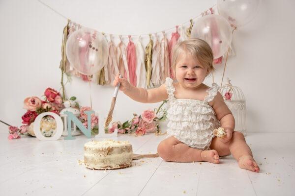 girly cake smash pink floral paper garland birthday Samphire Photography Horsham Sussex