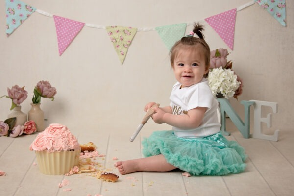 Classic cake smash by Samphire Photography Sussex flowers bunting bespoke