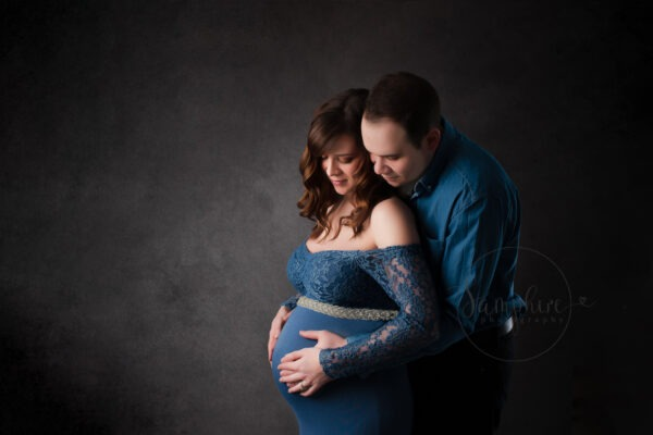 studio portrait of woman pregnant with twins wearing blue dress with partner by Samphire Photography