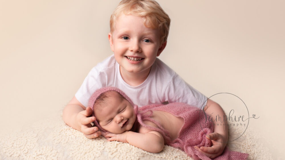 newborn baby shoot with sibling smiling
